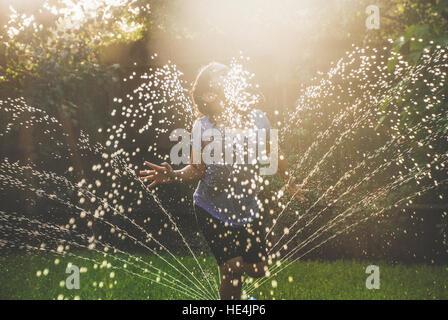 girl playing in sprinkler in suburban backyard - Stock Image