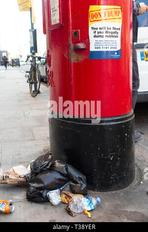 Irony - A dump of rubbish by a letter box under a sign ordering 'Don't Dump' - Stock Image