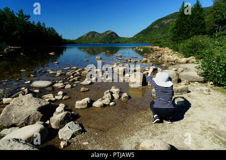 Woman taking a picture of Jordan Pond with her mobile phone. Acadia National Park, Maine, USA. - Stock Image