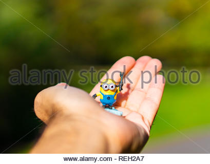 Poznan, Poland - October 7, 2018: Plastic yellow Minion toy figure standing on a open hand in soft focus outdoors. - Stock Image
