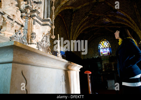 A female visitor to Palácio da Pena standing in front of the palace chapel's 16th-century alabaster and marble retable.  - Stock Image