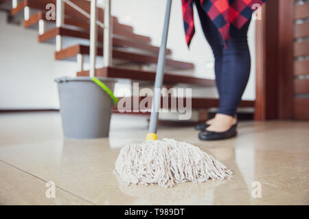 Woman is wiping the floor with mop with stairs in the background. - Stock Image