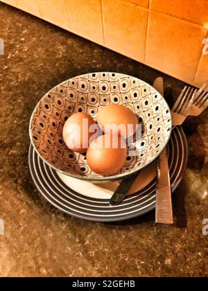 Three chicken eggs in a patterned bowl on a kitchen counter, next to knife and forks - Stock Image