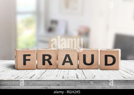 Fraud sign made of wooden blocks on a white desk in a bright room - Stock Image