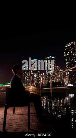 Side view of businessman sitting on bench against night view of city - Stock Image