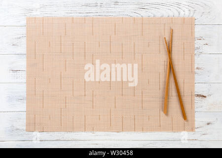 two sushi chopsticks with empty brown bamboo mat or wood plate on white wooden Background Top view with copy space. empty asian food background. - Stock Image