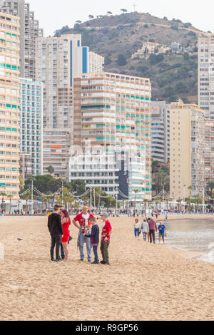 Benidorm, Costa Blanca, Spain, 25th December 2018. British tourists dress for the occasion on Christmas Day in this favourite getaway destination for Brits escaping the cold weather at home. Temperatures will be in the mid to high 20's Celsius today in this mediterranean hotspot. Group of people on beach in distance wearing Christmas jumpers. - Stock Image
