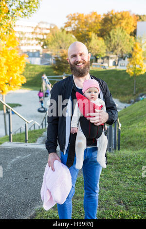 Portrait of father with baby girl in baby carrier - Stock Image