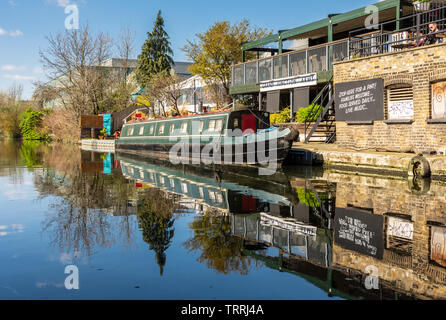 London, England, UK - March 24, 2019: A traditional narrowboat is moored on the Grand Union Canal beside Grand Junction Arms pub in North Acton. - Stock Image