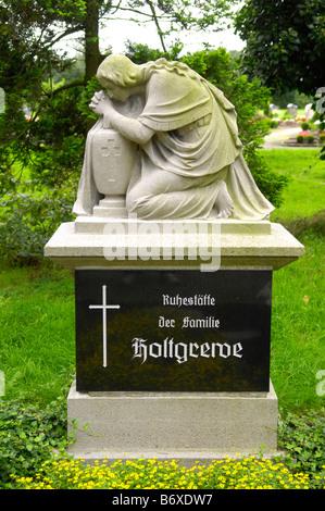 female statue headstone grave cemetery graveyard gothic germany deutschland sennelager kneel pray stone woman death - Stock Image