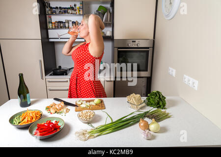 Woman in red dress drinking wine from glass in kitchen - Stock Image