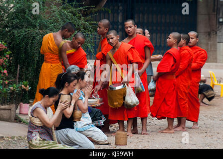 Buddhist monks receive alms each morning from local women, who thereby 'make merit' for themselves.  Pakse, - Stock Image