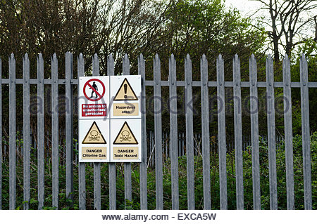 Hazard warning signs on fence around industrial plant handling dangerous toxic chemicals including chlorine. The - Stock Image