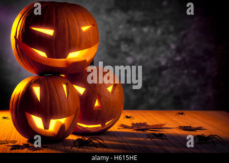 Halloween pumpkin still life, three carved gourds with glowing creepy faces on the table with many disgusting spiders - Stock Image