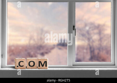 Com sign in a bright window with a view to a road going through a landscape - Stock Image