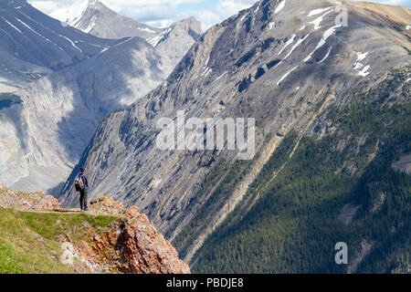 A teen hiker standing at the edge of Parker Ridge crest on the Icefields Parkway in Jasper National Park with the Canadian Rockies in the background. - Stock Image