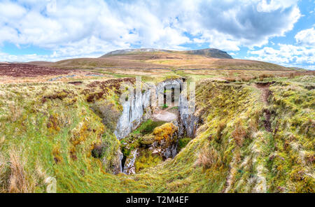 A large rock chasm with massive cliffs in a barren grassy landscape is seen below the peak of Pen-y-Ghent in the Peak District, England. - Stock Image