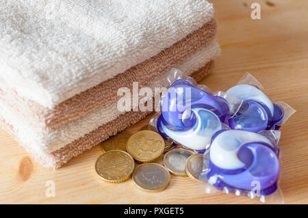 Saving concept: stack of washing capsules, clear towels and some euro coins - Stock Image