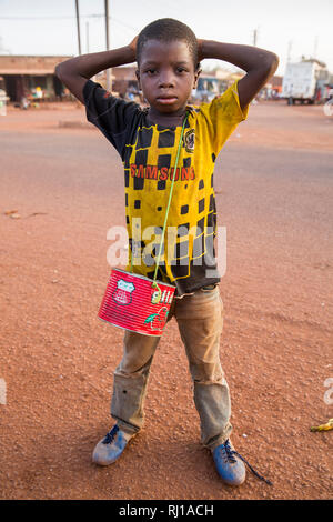 Yako, Burkina Faso; young boy with begging tin. - Stock Image
