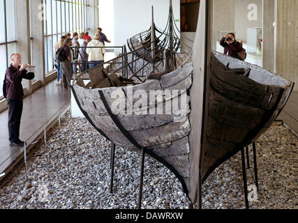 Visitors take a look at Viking ships from the 11th century, discoverd in the Roskilde fjord in 1962, in the ship - Stock Image