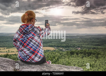 Successful female hiker taking photo on cliff edge. Cute girl on  rock making a photo on a smartphone. - Stock Image