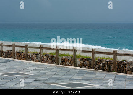 Empty promenade, clear azure waters of the Pacific Ocean washing over the pebbles, Chisingtan Scenic Area, Xincheng Township, Hualien County, Taiwan - Stock Image