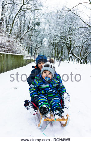 Poznan, Poland - January 26, 2019: Two young boys sitting on a wooden sled on snow at a park on a cold winter day. - Stock Image