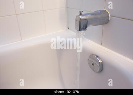 A bathroom shower stall with the tub faucet running water and copy space - Stock Image