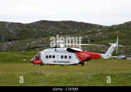 Stornoway based coastguard helicopter landed in a field - Stock Image