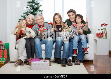 Family With Christmas Presents Sitting On Sofa - Stock Image