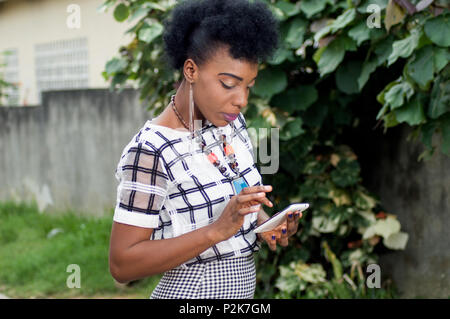 Beautiful young African business woman reading a text message on her mobile phone - Stock Image