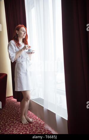 A ginger woman standing by the window and holding a cup of coffee - Stock Image