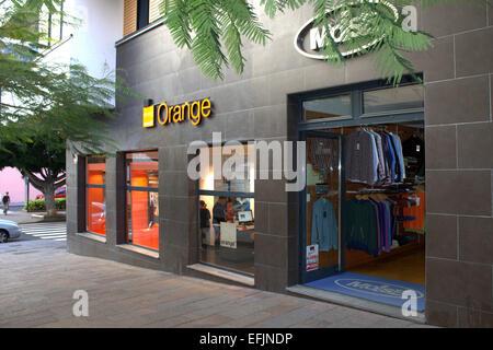 Four People shopping in an Orange Shop in La Palma. - Stock Image