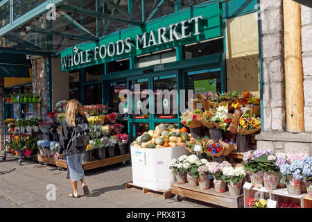 Young blond woman walking past the Whole Foods Market on West 4th Avenue  in the Kitsilano neighborhood of Vancouver, BC, Canada - Stock Image