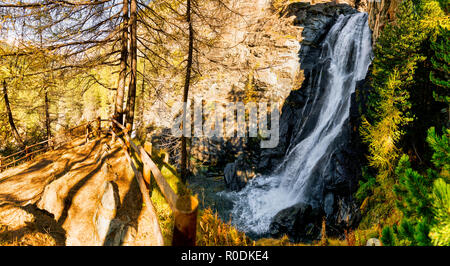 Wonderful waterfall in the forest in the mountains during the autumn season with light and shadows in the undergrowth - Stock Image