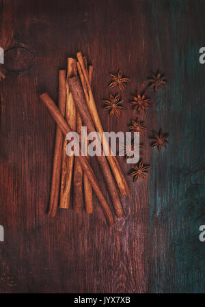 cinnamon sticks, star anise on old wooden background (dark, top view) - Stock Image