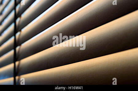 Closeup of wooden slats of a blind with natural sunshine shining through the gaps. The blinds are a little dusty. - Stock Image