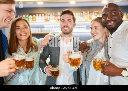 Group of friends having beer together in pub or bar after work - Stock Image