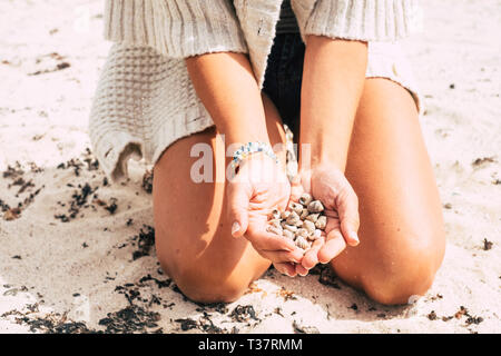 Caucasian woman on the sand at the beach holding and showing a lot of little marine shells under the sunny day - tourism and vacation and love for nat - Stock Image