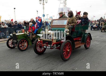 A 1904 Maxwell (centre) and a 1904 Peugeot (left), cross the finishing line together at the end of the 2018 London to Brighton Veteran Car Run - Stock Image