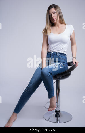 A girl in blue jeans and bare feet is sitting on a bar chair and posing in studio. Woman portrait and fashion concept - Stock Image