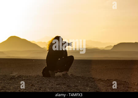 A photographer taking a picture of the sunset in the Wadi el gamal desert, Egypt. - Stock Image
