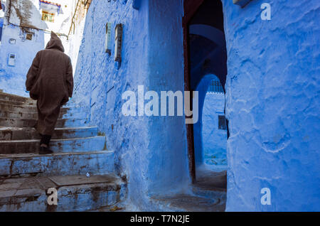 Chefchaouen, Morocco : A man wearing a trational djellaba walks in the alleyways of the blue-washed medina old town. - Stock Image