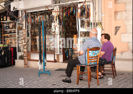 Greek couple sitting outside traditional shop selling komboloi (worry beads) Rethymno Crete Greece - Stock Image