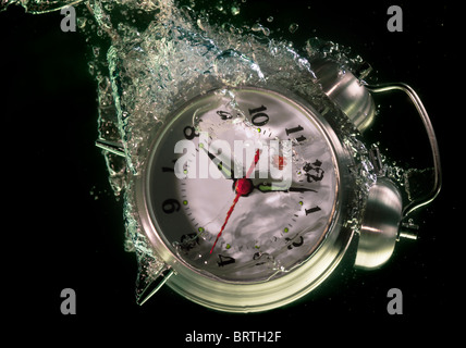 Alarm clock sinks underwater - Stock Image