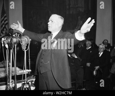 William Green standing and talking in front of microphones, gesticulating as he speaks passionately ca. 1936 - Stock Image