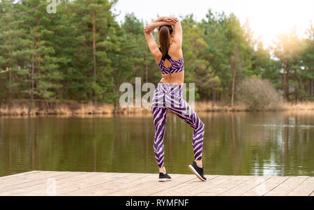 sporty woman standing on a jetty by a lake doing warm-up exercises. Back view. - Stock Image