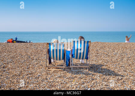BRIGHTON, UK - APRIL 8, 2017: Couple sitting in deckchairs on a sunny April day on Brighton beach in April 2017. - Stock Image