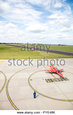 High angle view of man standing by Red Arrows airplane on RAF Scrampton, UK - Stock Image