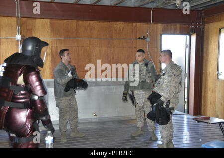 U.S. Air Force Staff Sgt. Micheal Sweeney (Center left), 144th Security Forces instructor, critiques Tech. Sgt. Daniel Mosqueda (Center right) and Airman 1st Class Jason Wundor during challenge and use of force exercises at the Fresno Police Department Regional Training Center Jan. 10, 2016. - Stock Image